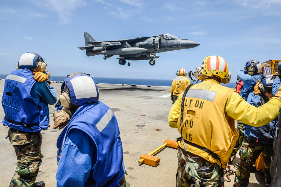 EAST CHINA SEA (JUNE 19, 2013) Sailors assigned to the amphibious assault ship USS Bonhomme Richard (LHD 6) shield their faces from jet exhaust as an AV-8B Harrier jet aircraft assigned to Marine Attack Squadron (VMA) 513 lands on the ship's flight deck. The Bonhomme Richard Amphibious Ready Group is conducting joint force operations in the U.S. 7th Fleet area of responsibility. (U.S. Navy photo by Mass Communication Specialist Seaman Apprentice Edward Guttierrez III)